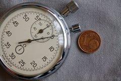 Moneda euro con una denominación de un centavo euro y cronómetro en el contexto gris del dril de algodón - fondo del negocio Imagenes de archivo
