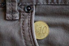Moneda euro con una denominación del centavo euro diez en el bolsillo de vaqueros grises gastados del dril de algodón Fotos de archivo libres de regalías