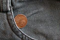 Moneda euro con una denominación del centavo euro dos en el bolsillo de vaqueros marrones gastados del dril de algodón Foto de archivo