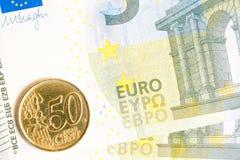 Moneda euro en nuevo billete de banco del euro cinco Fotos de archivo