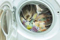 Moneda euro/europea, alta denominación en la lavadora, concepto del blanqueo de dinero imágenes de archivo libres de regalías