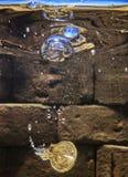 Moneda euro que cae en un pozo whising Imagen de archivo libre de regalías