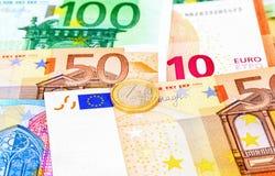 Moneda euro que miente sobre billetes de banco euro de la moneda Fotografía de archivo