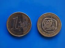 1 moneda euro, unión europea, Grecia sobre azul Foto de archivo