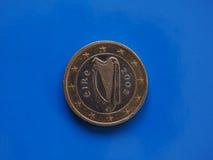 1 moneda euro, unión europea, Irlanda sobre azul Fotos de archivo