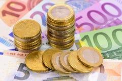Moneda euro y billetes de banco Fotografía de archivo