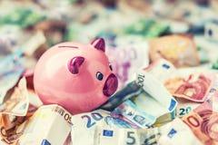 Moneda euro y hucha de los billetes de banco euro euro del dinero Imagen de archivo