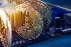 Moneda física de Bitcoin del oro en una tarjeta de vídeo del ordenador Nuevo cryptocurrency mundial independiente imagen de archivo libre de regalías