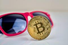 Moneda física del bitcoin del oro y vidrios rosados Imagenes de archivo