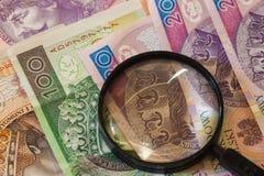 Moneda polaca y lupa de los billetes de banco del zloty Fotografía de archivo