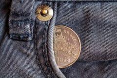 Moneda tailandesa con una denominación del baht cinco en el bolsillo de vaqueros azules obsoletos del dril de algodón Imagen de archivo