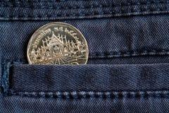 Moneda tailandesa con una denominación del baht cinco en el bolsillo de vaqueros del tejano azul oscuro Imagenes de archivo
