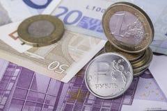 Moneda una rublo y la moneda europea: billetes de banco, monedas euro Imagen de archivo libre de regalías