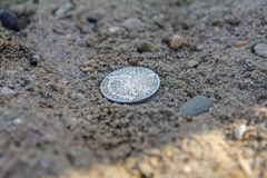 Moneda vieja encontrada en la orilla del río en la arena fotos de archivo