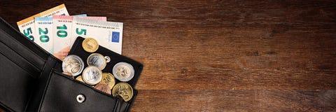 Moneda y billete de banco euro en cartera de cuero negra Fotos de archivo libres de regalías