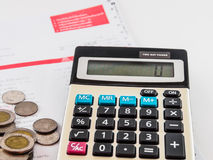 Moneda y calculadora en cuenta Foto de archivo