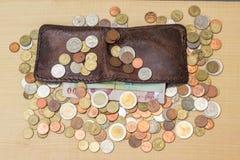 Moneda y papel del baht tailandés con la cartera de cuero marrón en vagos de la madera contrachapada Imagen de archivo