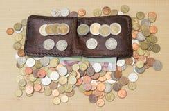 Moneda y papel del baht tailandés con la cartera de cuero marrón en vagos de la madera contrachapada imagenes de archivo
