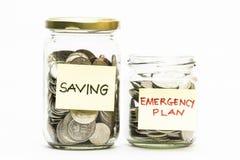 Monedas aisladas en tarro con plan de emergencia y la etiqueta del ahorro. Imágenes de archivo libres de regalías