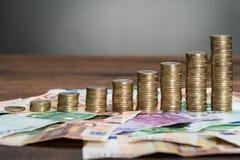 Monedas apiladas dispuestas en billetes de banco Foto de archivo libre de regalías