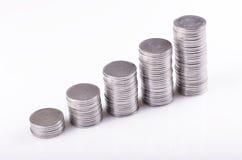 Monedas apiladas en el aumento Fotografía de archivo