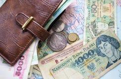 Monedas, billetes y una cartera de cuero en el fondo foto de archivo