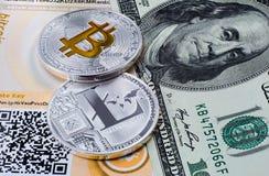 Monedas Bitcoin y Litecoin en el fondo del billete de dólar Fotografía de archivo