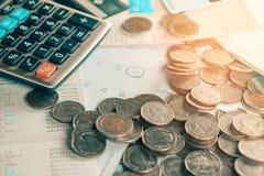 Monedas, calendario del plazo, libro de cuentas de ahorro, calculadora, tarjeta de crédito en la tabla, fondo del reembolso de la foto de archivo
