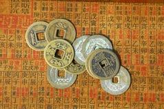 Monedas chinas antiguas en un texto detrás Imagenes de archivo