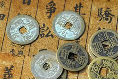 Monedas chinas antiguas en un texto detrás Imágenes de archivo libres de regalías