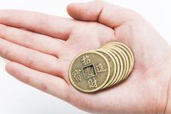 Monedas chinas de bronce antiguas en la mano del hombre imagenes de archivo