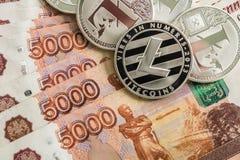 Monedas crypto de plata Litecoin LTC, rublos rusas Las monedas del metal se presentan en un fondo liso el uno al otro, cerca Fotografía de archivo