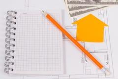 Monedas dólar, libreta y diagramas eléctricos, alquilando o vendiendo la casa o el concepto plano foto de archivo