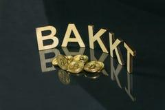 Monedas de Bitcoin delante de la muestra del bakkt hecha de la madera con la reflexión en la tabla, Eslovenia - 27 de diciembre fotos de archivo libres de regalías