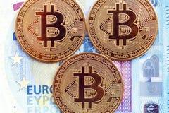 Monedas de Bitcoin en el fondo de 20 cuentas euro imagen de archivo libre de regalías