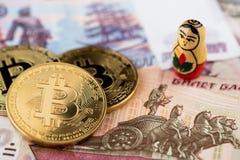 Monedas de Bitcoin en los billetes de banco rusos con el cierre nacional ruso de la muñeca A encima de la imagen de bitcoins con  fotos de archivo