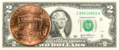 monedas de 1 centavo contra anverso del billete de banco de 2 nosotros-dólares foto de archivo libre de regalías