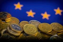 Monedas de centavos euro y euro contra la perspectiva de la bandera Fotografía de archivo