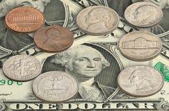 Monedas de Estados Unidos en los billetes de dólar uno Fotografía de archivo
