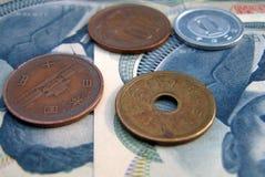 Monedas de JJapanese y 100 cuentas de los Yenes Fotografía de archivo libre de regalías