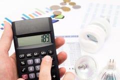 Monedas de la calculadora y del euro de la pizca de la bombilla Foto de archivo libre de regalías