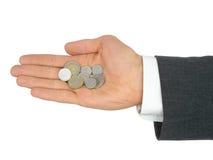 Monedas de la explotación agrícola de la mano del hombre de negocios Foto de archivo libre de regalías