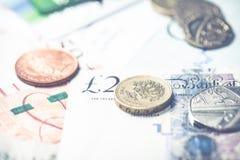 Monedas de la libra esterlina sobre notas fotos de archivo