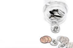 Monedas de la moneda americana que salen del tarro del ahorro fotos de archivo libres de regalías