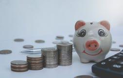 Monedas de la pila, calculadora con la hucha Financiero y ahorro Fotografía de archivo libre de regalías