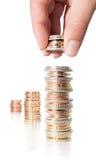 Monedas de la pila con la mano - ingresos cada vez mayores Fotos de archivo