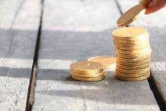 Monedas de la pila con la mano Imágenes de archivo libres de regalías