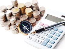 Monedas de la pila y pluma de bola en la calculadora Imagenes de archivo