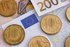 Monedas de la rublo en billetes de banco euro Imagen de archivo libre de regalías