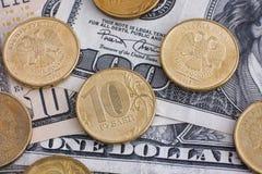 Monedas de la rublo en billetes de dólar Foto de archivo